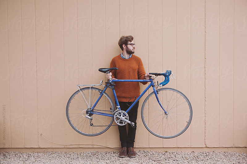 Young Man Holds Blue Bike